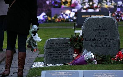 A member of the public looks on at a memorial stone in memory of the victims of the Pan Am flight 103 bombing in the garden of remembrance at Dryfesdale Cemetery, near Lockerbie, Scotland, Saturday, Dec. 21, 2013. (Photo credit: AP/Scott Heppell)