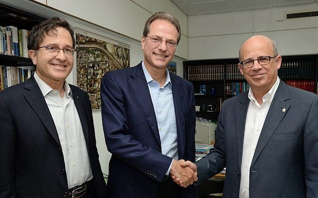 Flanked by Broadcom Corporate Vice-President Dr. Shlomo Markel (L.), Broadcom Chairman and CTO Dr. Henry Samueli (C.) shakes hands with Tel Aviv University President Prof. Joseph Klafter at the signing of an agreement between TAU and the Broadcom Foundation that will focus on finding breakthrough solutions for cyber threats (Photo credit: Courtesy)