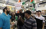 """Palestinian protesters hold up flags and a sign reading """"boycott occupation and its products"""" during a protest at a Rami Levy supermarket in the West Bank Jewish settlement of Modiin Illit, October 24, 2012 (photo credit: Issam Rimawi/Flash90)"""