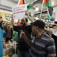 "Palestinian protesters hold up flags and a sign reading ""boycott occupation and its products"" during a protest at a Rami Levy supermarket in the West Bank Jewish settlement of Modiin Illit, October 24, 2012 (photo credit: Issam Rimawi/Flash90)"