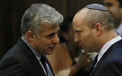 Yair Lapid (left) speaking with Naftali Bennett (right) during a plenum session in the Knesset, April 22, 2013. (Miriam Alster/Flash90)