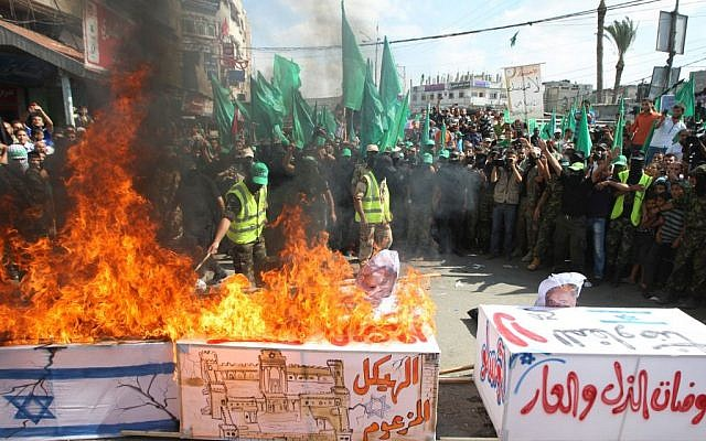 Hamas activists burn a coffin draped in an Israeli flag, during a rally marking the 13th anniversary of the so-called Al-Aqsa uprising or Second Intifada, in the refugee camp of Nusairat, central Gaza Strip, Sept. 27 2013 (photo credit: Abed Rahim Khatib/Flash90)