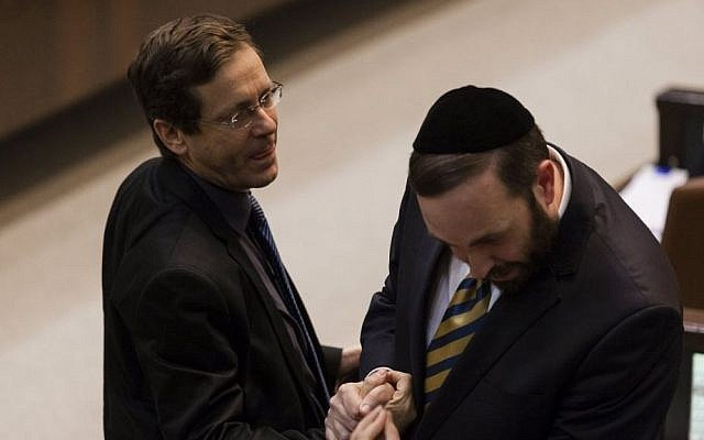 Newly-elected Labor Party leader Isaac Herzog (left) speaks to ultra-Orthodox Shas MK Ariel Atias during a Knesset plenum session, November 2013. (photo credit: Flash90)