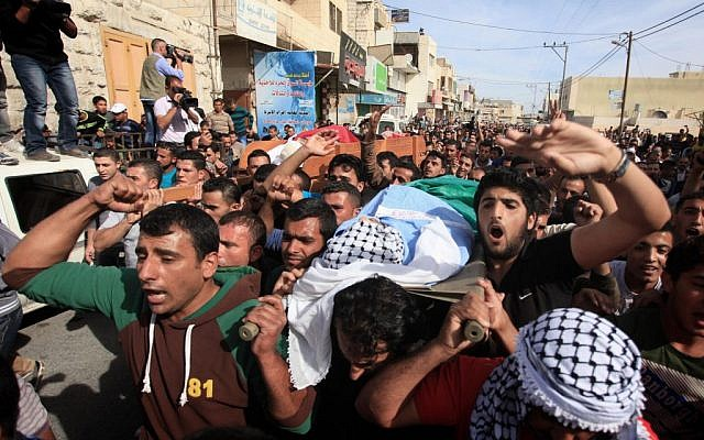 Mourners attend the funeral of Palestinian militants Khaled al-Najjar and Mussa Fanasheh on November 27, 2013 in the West Bank village of Yatta, one day after they were shot dead, along with another Palestinian activist (photo credit: Issam Rimawi/Flash90)