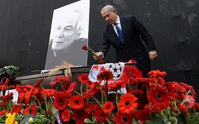 Prime Minister Benjamin Netanyahu lays a flower on the coffin of Israeli legendary singer Arik Einstein (photo credit: Kobi Gideon/GPO/FLASH90)