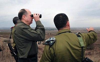 Defense Minister Moshe Ya'alon looks into Syrian territory from the Golan Heights on December 3, 2013. (Photo credit: Ariel Hermoni/Ministry of Defense/Flash 90)