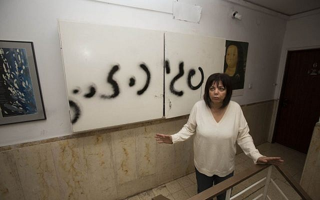 Peggy Cidor standing next to graffiti outside her home Thursday. (photo credit: Yonatan Sindel/Flash90)