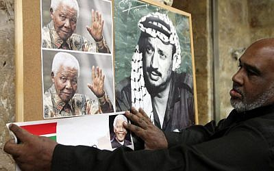 A Palestinian man hangs a picture of Nelson Mandela next to a portrait of Yasser Arafat at a memorial service in Jerusalem's Old City, December 8, 2013 (photo credit: Sliman Khader/Flash90)