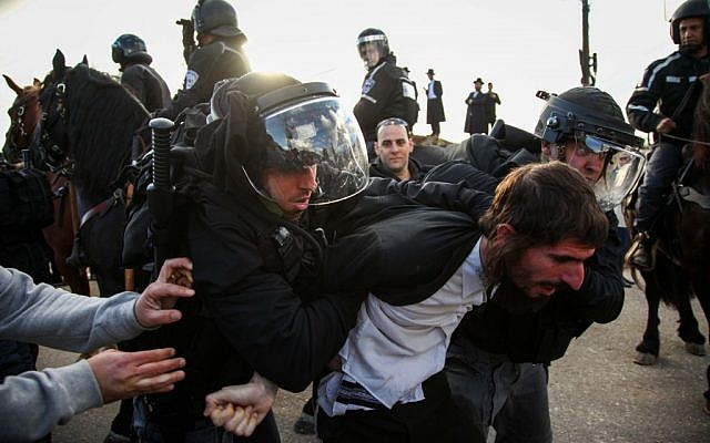An Ultra Orthodox boy is arrested during a large protest outside the military prison, south of Haifa December 9, 2013. (photo credit: Avishag Shaar Yeshuv/Flash 90)