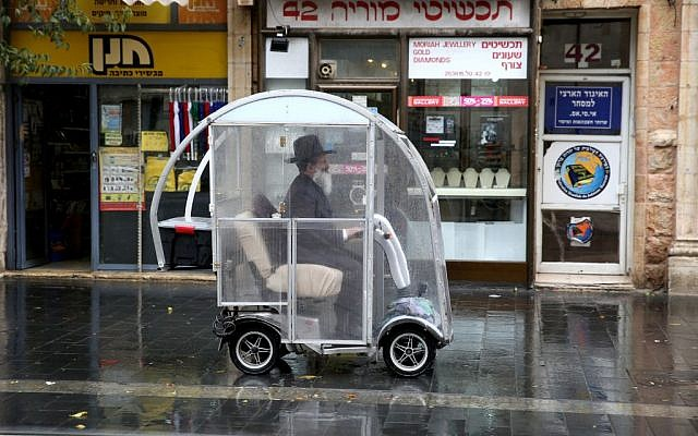 A man driving a scooter through the rain in Jerusalem Wednesday. (photo credit: Hadas Parush/Flash90)