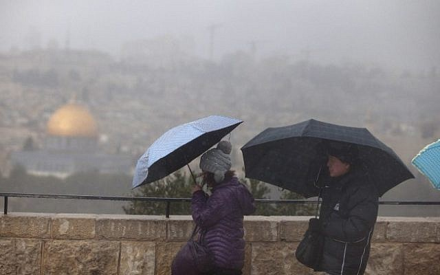 Tourists take cover under umbrellas while visiting the Mount of Olives overlooking Jerusalem's Old City and the Dome of the Rock, on a stormy Wednesday, December 11, 2013. (photo credit: Lior Mizrahi/Flash90)