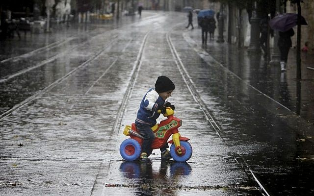A toddler rides a tricycle through puddles on Jaffa Road in Jerusalem, Wednesday, December 11, 2013 (photo credit: Miriam Alster/Flash90)