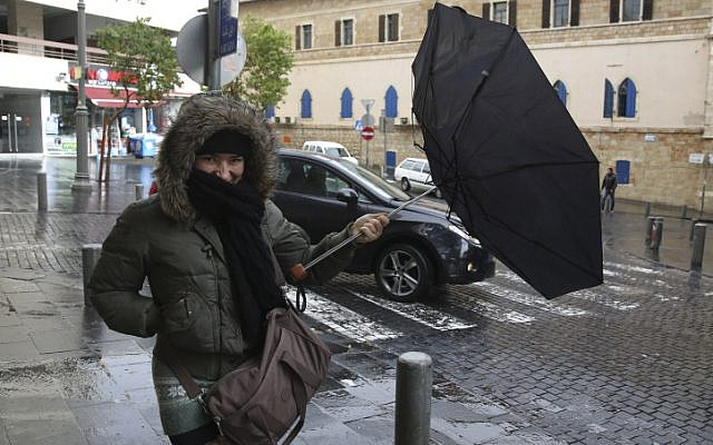 A woman holds an umbrella to protect herself from the rain, on a winter day in the center of Jerusalem. December 11, 2013. (photo credit: Nati SHohat/FLASH90)