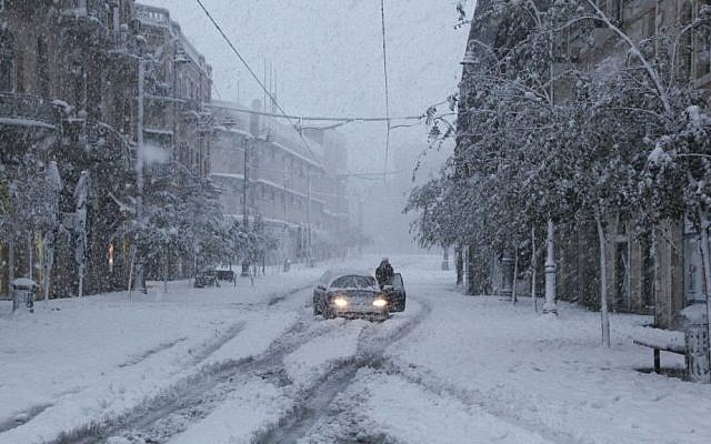 A car gets stuck on a snow-packed road during a major snowstorm in Jerusalem (photo credit: Meital Cohen/Flash90)