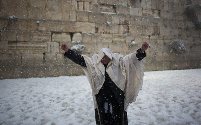 A man prays at the Western Wall in Jerusalem's Old City, on a snowy winter morning. December 13, 2013. (Photo credit: Yonatan Sindel/Flash90)
