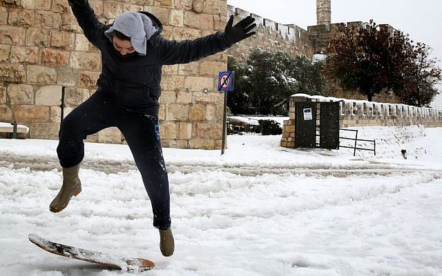 A young boy skates at Jaffa  Gate outside the Old City of Jerusalem, on the third day of the major snowstorm that hit the capital, Saturday, December 14, 2013. (photo credit: Hadas Parush/Flash 90)