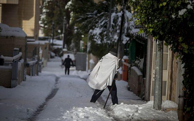 A man in a prayer shawl walks in the snow in Jerusalem on Saturday, December 14, 2013. (photo credit: Yonatan Sindel/Flash90)