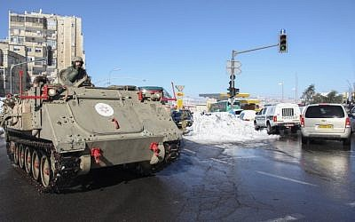 An IDF armored personnel carrier is seen clearing a snow-covered street in Jerusalem after a major snow storm hit the city over the weekend, December 15, 2013 (photo credit: Meital Cohen/Flash90)
