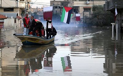 Palestinians take a boat through flooded streets in Gaza City, December 17, 2013 (photo credit: Wissam Nassar/Flash90)