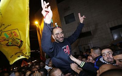 Palestinian prisoner Samer al-Issawi, who held a hunger strike for several months, flashes the 'V' for victory sign as he celebrates his release from an Israeli jail in the Arab Jerusalem neighborhood of Issawiya, on December 23, 2013. (photo credit: Sliman Khader/Flash90)