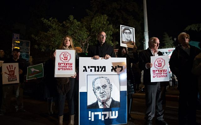 "Demonstrators, some of them relatives of Israelis killed by Palestinians, protest against the upcoming Palestinian prisoner release near the Prime Minister's residence in Jerusalem on December 28, 2013. The placard showing a drawing of Benjamin Netanyahu says in Hebrew: ""Not a leader, [a] liar.""  (Photo credit: Yonatan Sindel/Flash90)"
