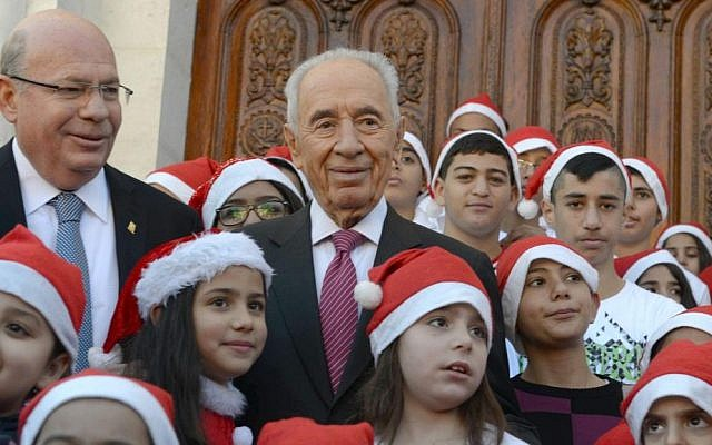 President Shimon Peres, center, with Christian schoolchildren in Ramle, on December 22, 2013 (photo credit: Mark Neiman/GPO)