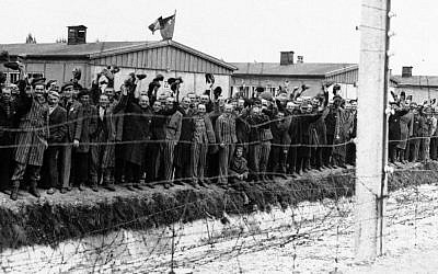In this undated photo, prisoners at the electric fence of the Dachau concentration camp in Germany cheer on the arriving Americans (photo credit: AP/File)