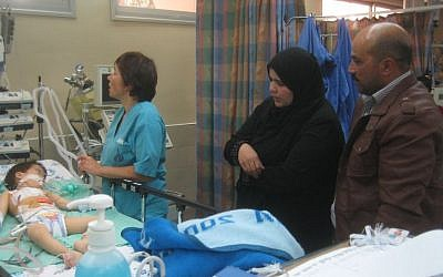 Mahmoud Abu Danash (right) and his wife Lubna stand beside the bed of their son, Muath, in the ICU at Holon's Wolfson Medical Center on Wednesday, December 25, 2013. (photo credit: Ilan Ben Zion/Times of Israel staff)