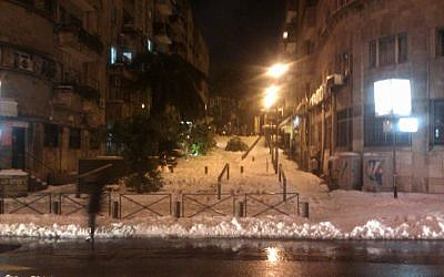 Jerusalem's Shatz Street pedestrian mall covered in snow and downed tree limbs, Saturday night, December 14, 2013 (photo credit: Ilan Ben Zion/Times of Israel)