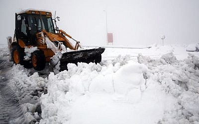 A tractor plows snow on the road at the Al Hader intersection in the West Bank, Saturday, December 14, 2013. (photo credit: Nati Shohat/Flash 90)