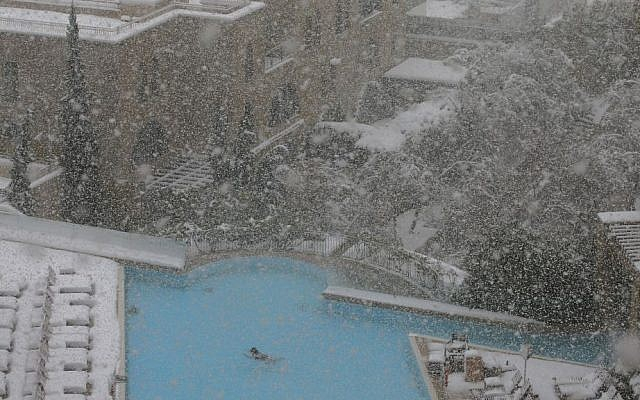 A woman swims in the pool at the David Citadel Hotel during a snowstorm in Jerusalem, Friday, December 13, 2013. (photo credit: AP/Brian Snyder, Pool)