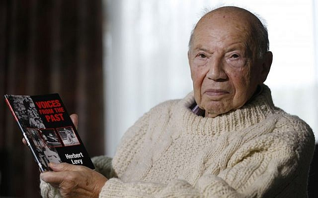 Herbert Levy, 84, who was brought to England by Kindertransport from Berlin in Germany in 1939 to escape Nazi persecution, holds a copy of his book 'Voices from the Past' at his home in London. (photo credit: AP Photo/Kirsty Wigglesworth)