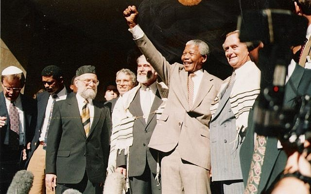 Nelson Mandela salutes the crowd at the Green and Sea Point Hebrew Congregation in Cape Town on a visit shortly after being elected South Africa's president in 1994. Joining Mandela, from left, are Rabbi Jack Steinhorn; Israel's ambassador to South Africa, Alon Liel; Chief Rabbi Cyril Harris; and Mervyn Smith, chairman of the South African Jewish Board of Deputies. (photo credit: SA Rochlin Archives, SAJBD)