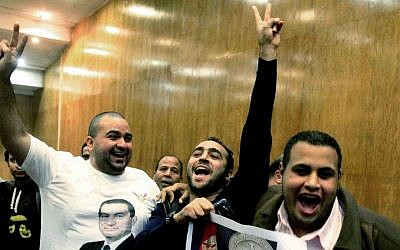 Egyptian supporters of former leader Hosni Mubarak celebrate after a court acquitted Mubarak's two sons and his last prime minister of corruption charges, judiciary officials said at a court, in Cairo, Egypt, on Thursday, December 19, 2013. (photo credit: AP Photo/Ahmed Abd El Latif, El Shorouk)