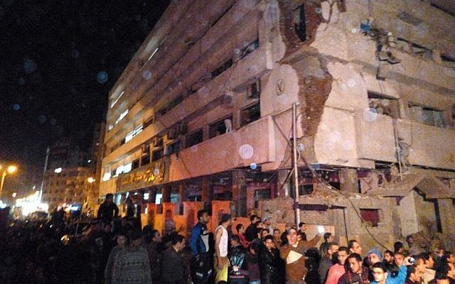 Egyptians gather after a powerful explosion believed to be caused by a car bomb rocked a police headquarters in the Nile Delta city of Mansoura, 110 kilometers (70 miles) north of Cairo early on Tuesday, December 24. 2013. (photo credit: AP)
