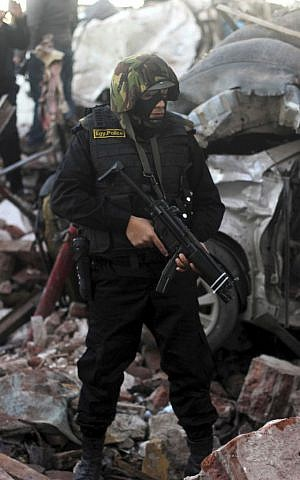 An Egyptian policeman stands guard at the site of an explosion at a police headquarters building in the Nile Delta city of Mansoura, 110 kilometers (70 miles) north of Cairo, Egypt, Tuesday, December 24, 2013. (photo credit: AP/Mostafa el-Shemy)