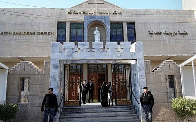 Iraqi police officers guard the entrance of St. Joseph's Chaldean Church before a Christmas mass in Baghdad, Iraq, Wednesday, Dec. 25, 2013. (photo credit: AP/Karim Kadim)