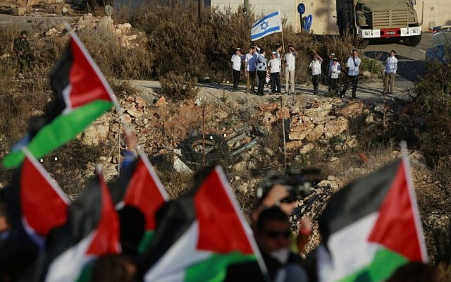 Israeli Jewish settlers hold an Israeli flag while Palestinian protesters wave Palestinian flags during a protest against the Prawer Plan, near the Israeli settlement of Beit El on Saturday, November 30, 2013. (photo credit: AP/Majdi Mohammed)