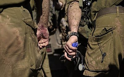 An Israeli army paramedic stands with a bloodied hand after treating a civilian shot near the Israel-Gaza border, Tuesday, Dec. 24, 2013. (photo credit: AP/Tsafrir Abayov)
