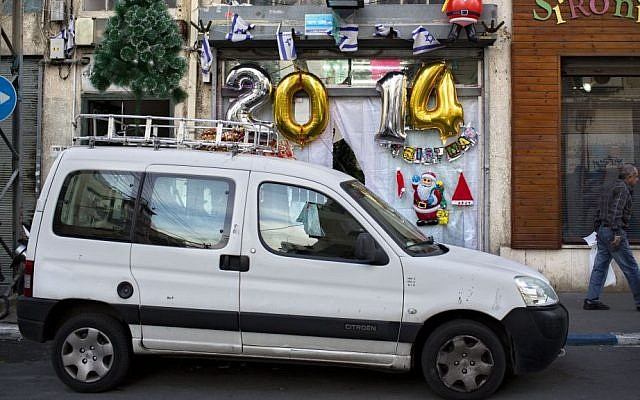 A man walks past a shop selling decorations ahead of New Year's Eve in Tel Aviv, Israel, Monday, Dec. 30, 2013. (AP Photo/Oded Balilty)