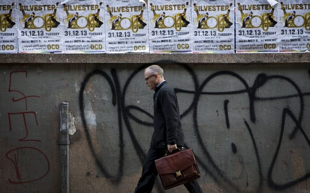 A man walks past posters advertising a New Year's Eve party in Tel Aviv, Israel, Monday, Dec. 30, 2013. In Israel, the somber, soul-searching and autumnal new year of the lunar Jewish calendar overshadows the Gregorian's Jan. 1. (AP Photo/Oded Balilty)