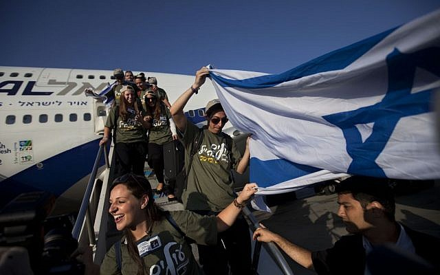 Jewish immigrants from the US wave an Israeli flag as they arrive at the Ben Gurion airport near Tel Aviv, Israel, Aug. 14, 2012 . (photo credit: AP/Oded Balilty, File)