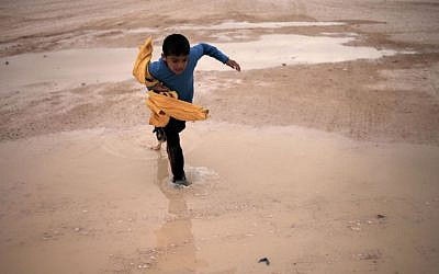 A Syrian boy crosses a water puddle at the Zaatari refugee camp, in Mafraq, Jordan, on Tuesday (photo credit: AP/Mohammad Hannon)