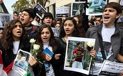 Lebanese students at the private Hariri High School, named after a prominent assassinated Sunni leader, chant slogans and hold photos of 16-year-old Mohammed Shaar, who was one of seven people killed in a car bomb that ripped through the upscale downtown district of Beirut, during a sit-in at the scene of the explosion in Beirut, Lebanon, Monday, Dec. 30, 2013. (AP Photo/Bilal Hussein)
