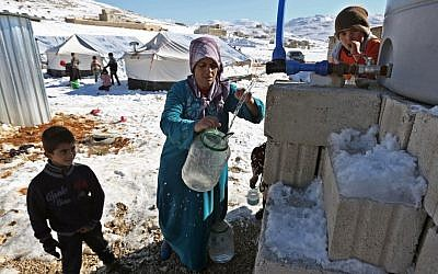 A Syrian refugee fetches water at a refugee camp in the eastern Lebanese border town of Arsal, Lebanon, on Sunday, December, 15, 2013. (photo credit: AP/Bilal Hussein)