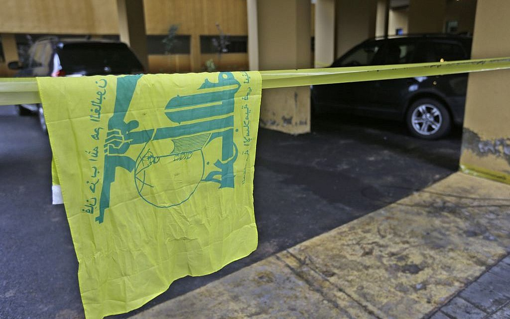 A Hezbollah flag hangs on yellow police tape sealing off the scene where Hassan al-Laqis, a senior commander for the Lebanese militant group Hezbollah, was gunned down outside his home, some two miles (three kilometers) southwest of Beirut, Lebanon on Wednesday, December 4, 2013.  (photo credit: AP/Hussein Malla)