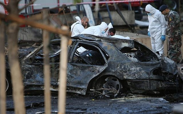 Lebanese army investigators in white coveralls inspect the scene of an explosion in central Beirut, Lebanon, Friday, Dec. 27, 2013, in which Mohammad Chatah, a senior aide to former Lebanese Prime Minister Saad Hariri, was killed. (Photo credit: AP/Hussein Malla)