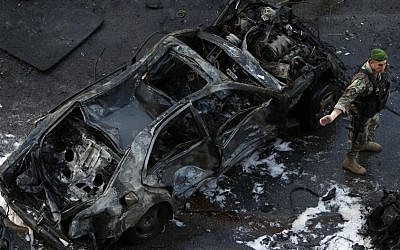 A Lebanese Army soldier stands next to a destroyed car at the scene of an explosion in central Beirut, Lebanon, Friday, Dec. 27, 2013, in which Mohammad Chatah, a senior aide to former Lebanese prime minister Saad Hariri, was killed. (photo credit: AP/Hussein Malla)