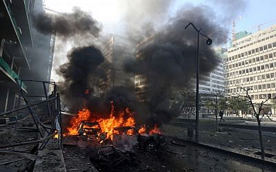 Flames blaze from vehicles at the scene of the explosion in Beirut, Lebanon, Friday, Dec. 27, 2013. (Photo credit: AP/Bilal Hussein)