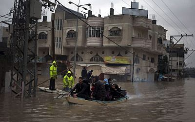 Palestinian rescue members evacuate residents using a fishing boat following heavy rains in Gaza City, Saturday, Dec. 14, 2013 (photo credit: AP/Khalil Hamra)